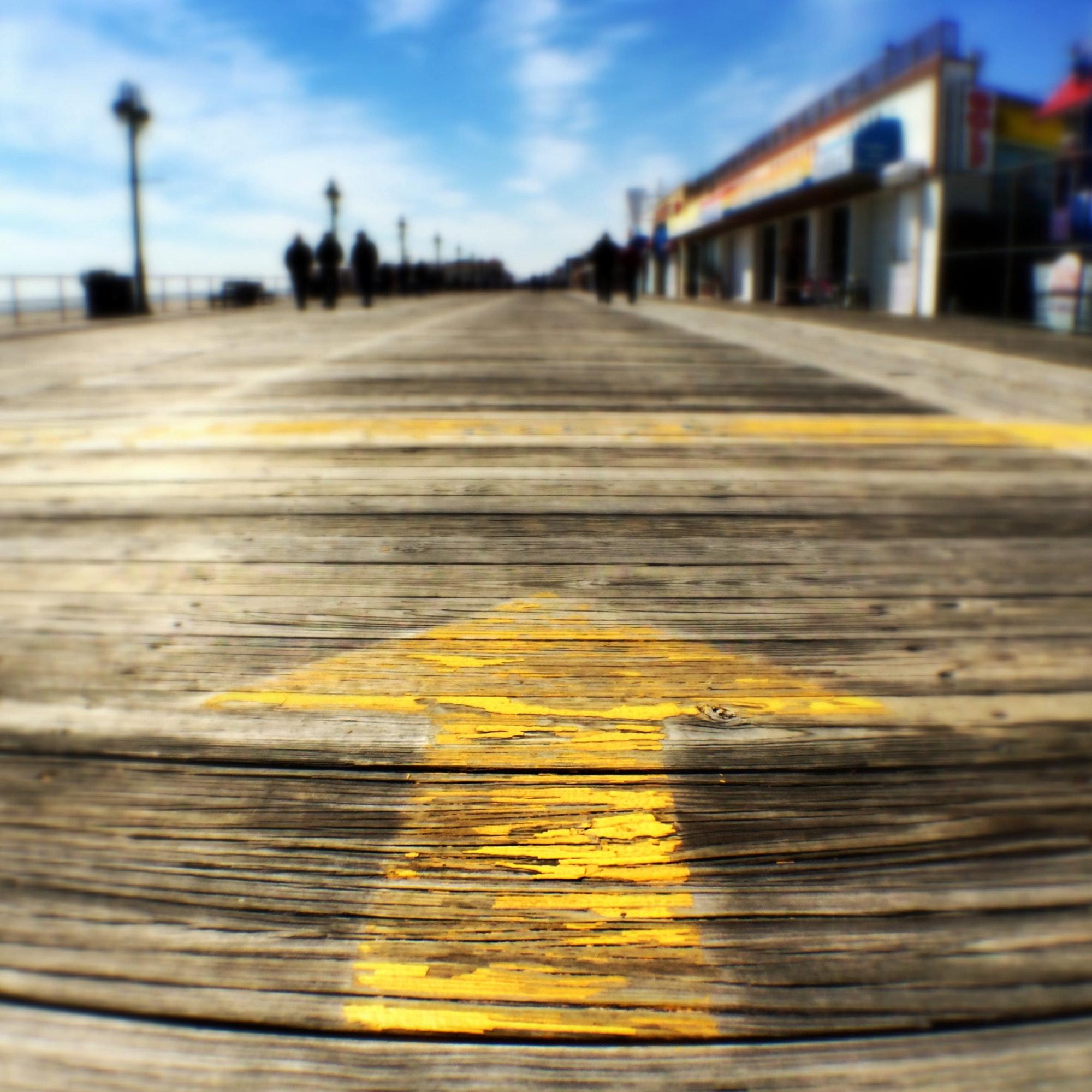 Arrow sign on wooden pier