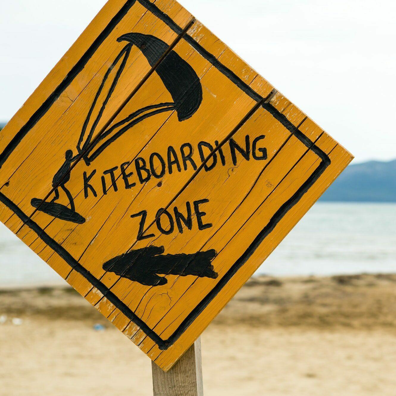Kiteboarding, wooden kitesurfing sign on beach