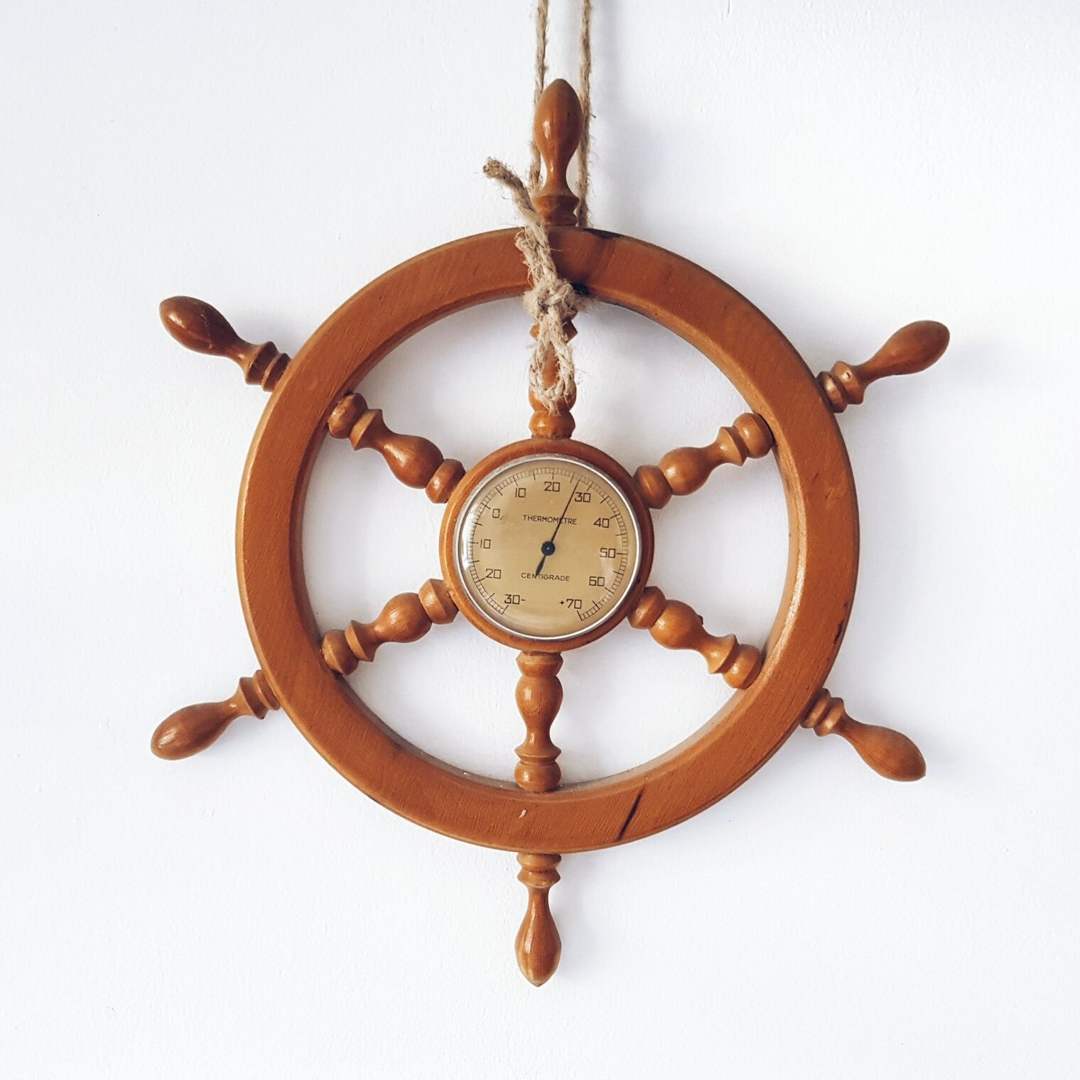 Wooden ship steering wheel, helm, hanging on white wall.